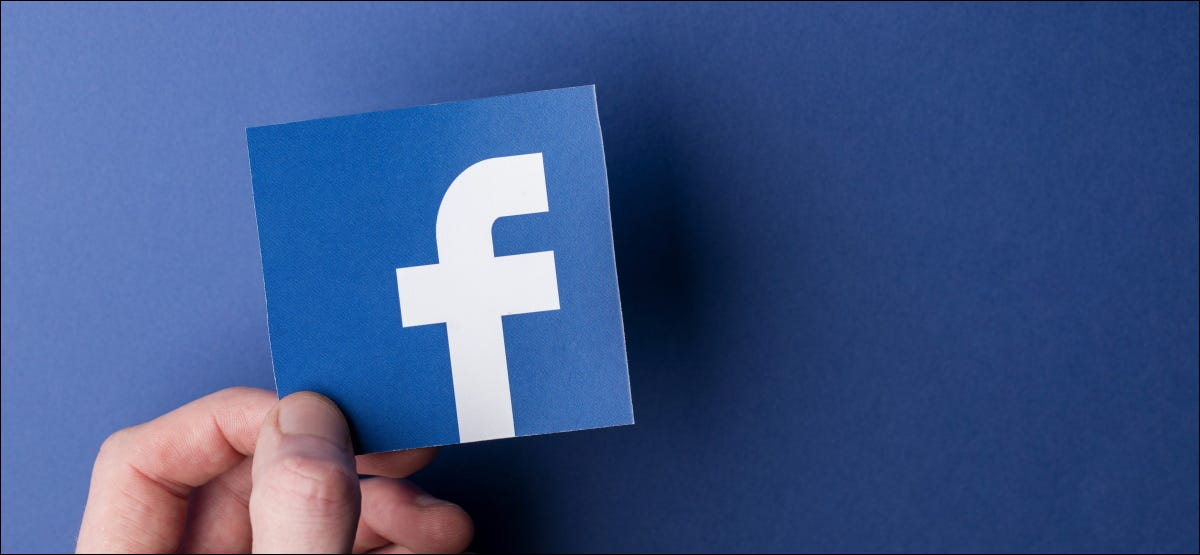 Eine Hand, die ein auf einem Blatt Papier gedrucktes Facebook-Logo hält.