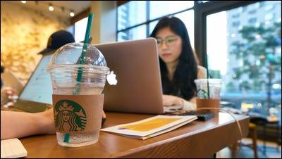 Leute, die in einem Starbucks-Restaurant an Laptops arbeiten.