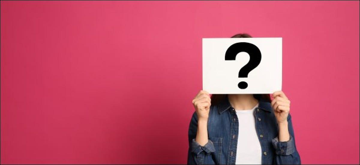 Eine Frau hält sich ein Fragezeichen vors Gesicht.