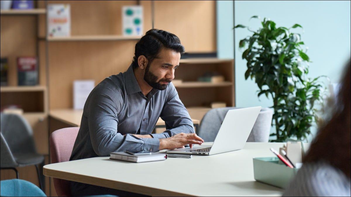 Ein Mann, der in einem Büro an einem Laptop arbeitet.