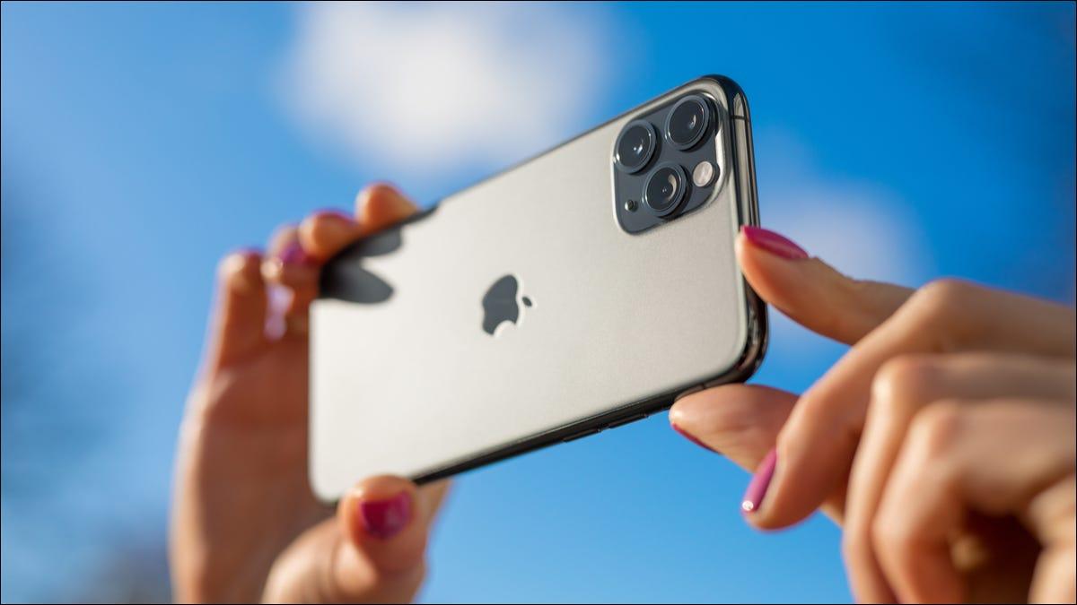 Eine Person, die draußen mit einem iPhone ein Foto macht.