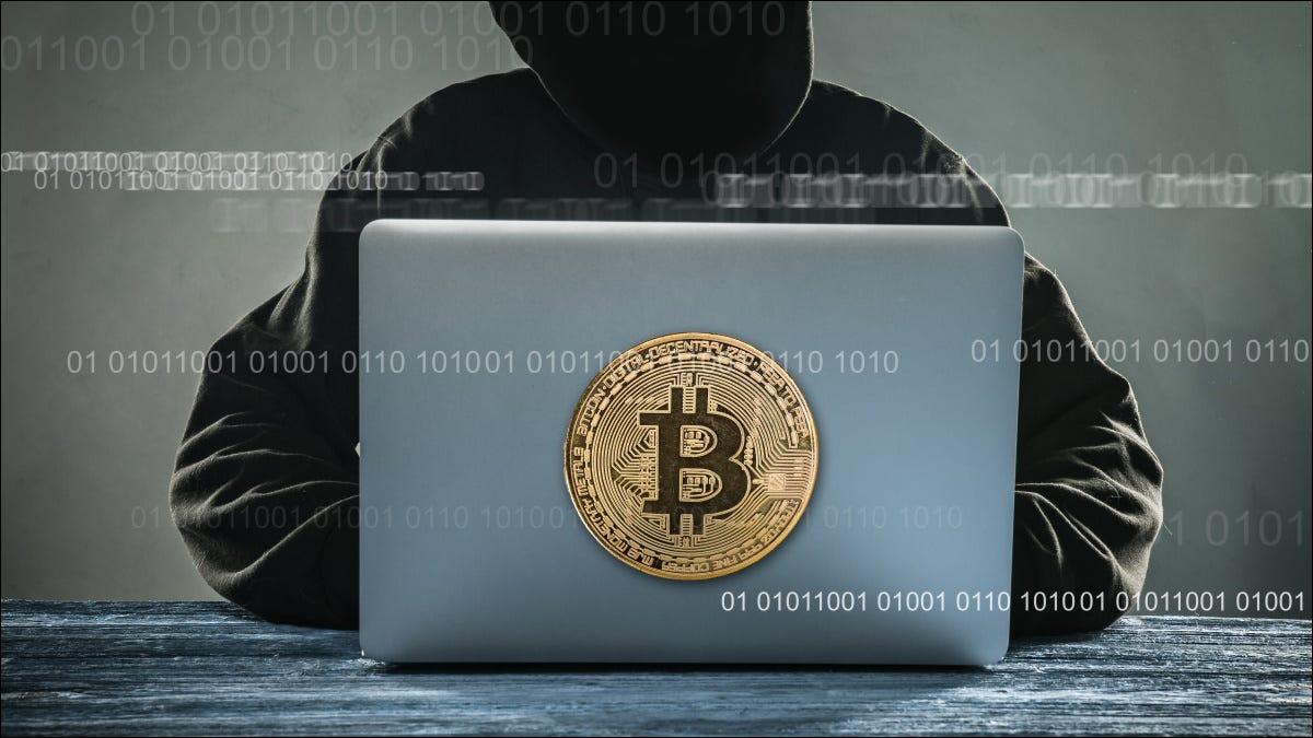 """Ein stilisierter anonymer """"Hacker"""", der einen Laptop mit einer Bitcoin-Illustration verwendet."""