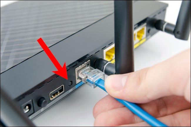 Roter Pfeil, der auf die Reset-Taste eines Heimnetzwerk-Routers zeigt