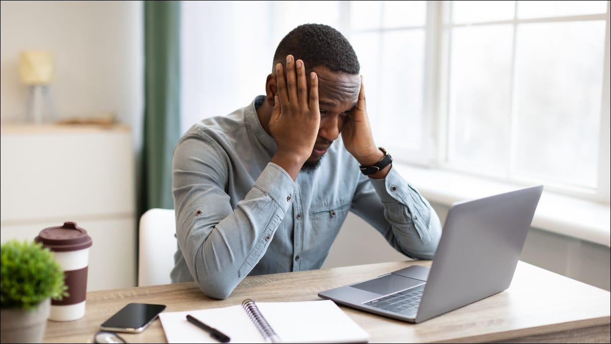 Mann, der mit Laptop am Schreibtisch sitzt und frustriert seinen Kopf umklammert